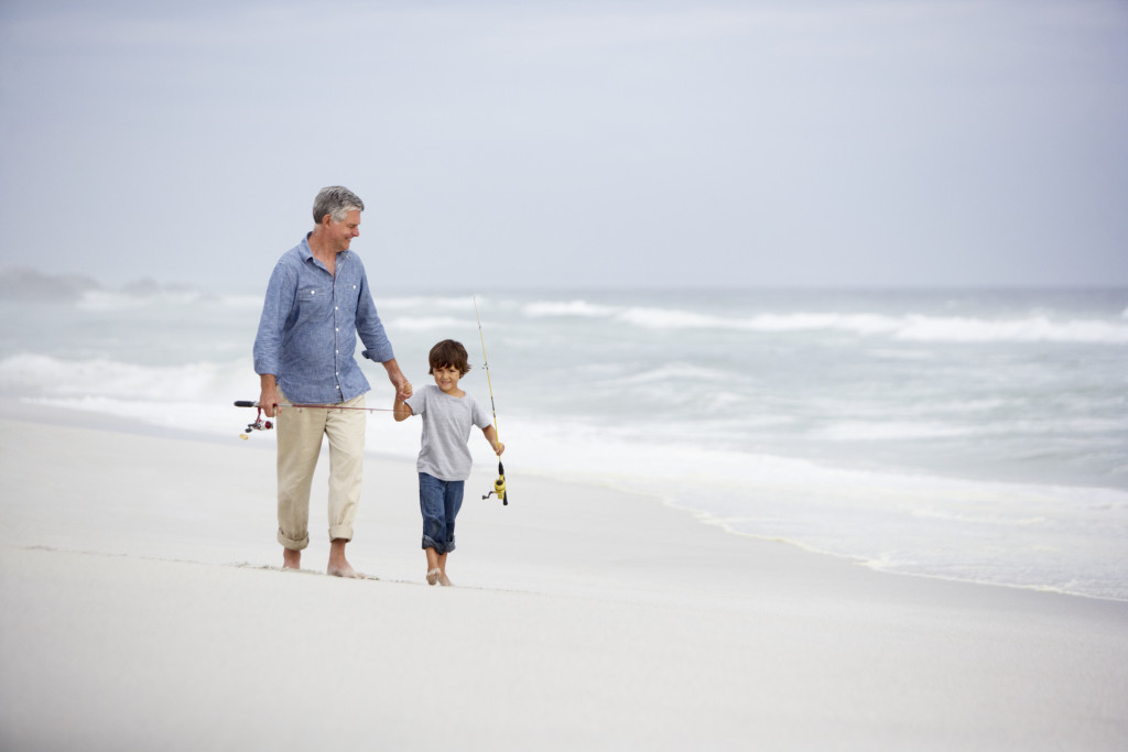 Senior man and grandson walking on beach